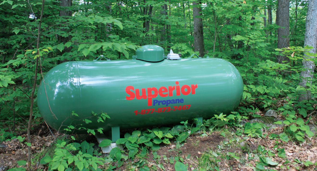 Green Superior Propane Tank in a Forested Area