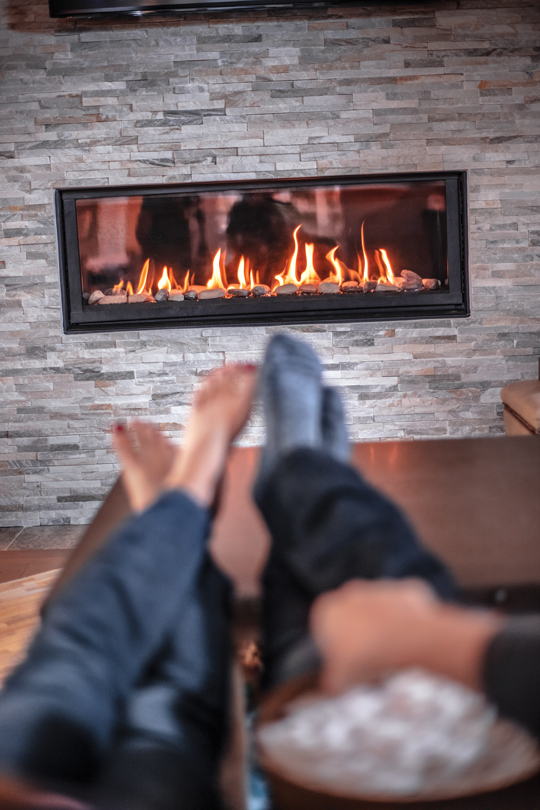 Couple sitting on a couch in their living room eating popcorn sitting next to propane fireplace.