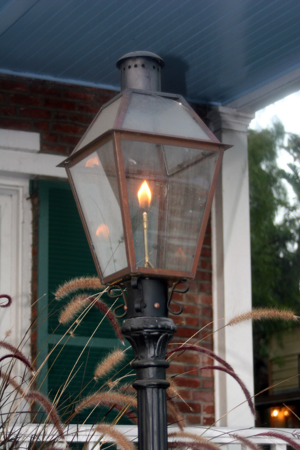 A propane-powered gas lamp in front of a brick house.