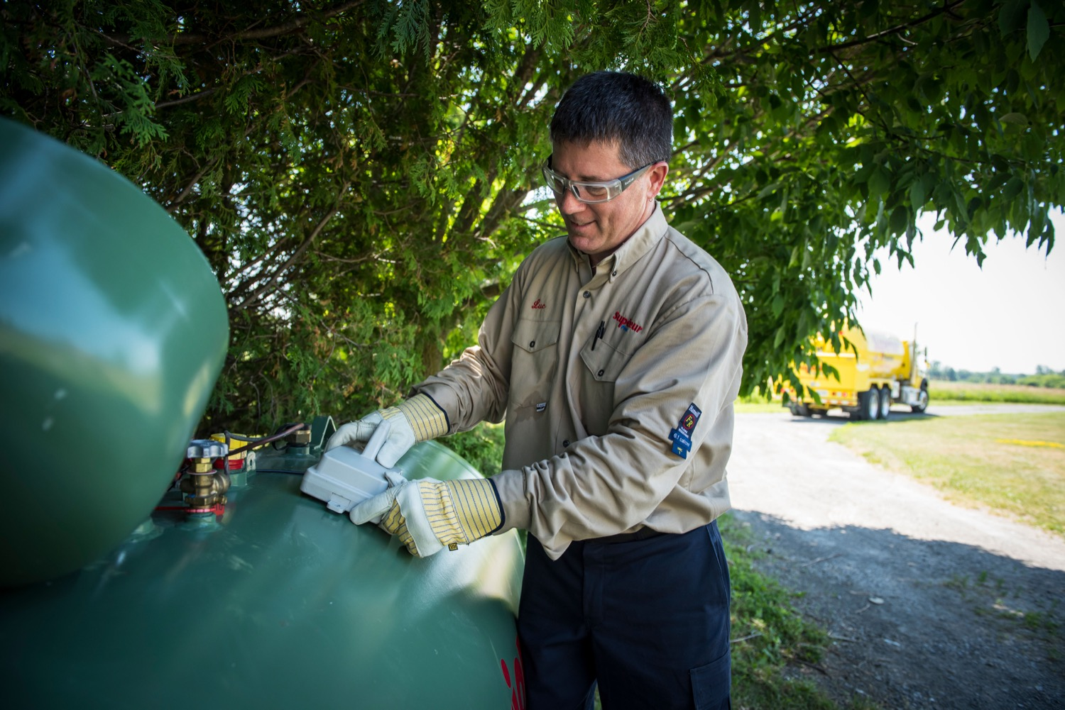 Superior Propane employee installing a smart tank monitor on a residential propane tank.