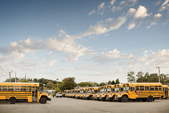 Large fleet of yellow school buses parked in a lot.