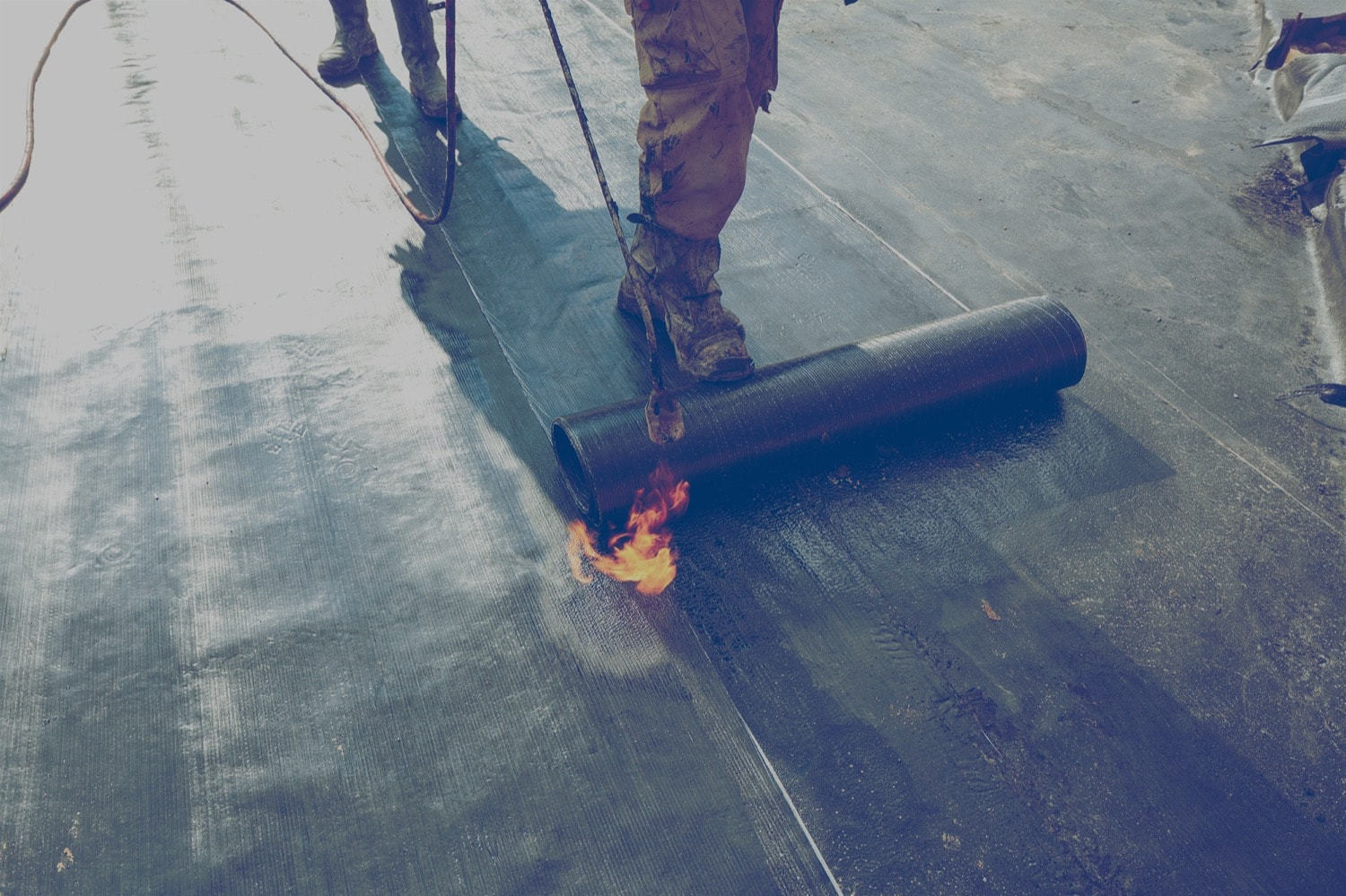 Construction worker using a hand-held propane torch to heat bitumen to create a waterproof seal on a roof.