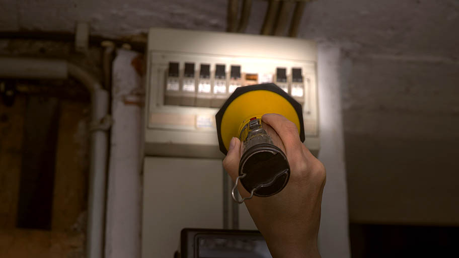 Person holding a flashlight to illuminate a circuit breaker in a basement.