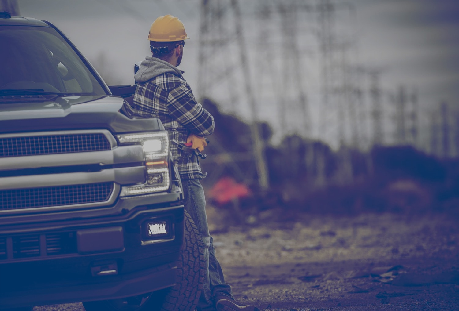 Construction worker standing beside a pickup truck holding a hammer and looking at power lines.