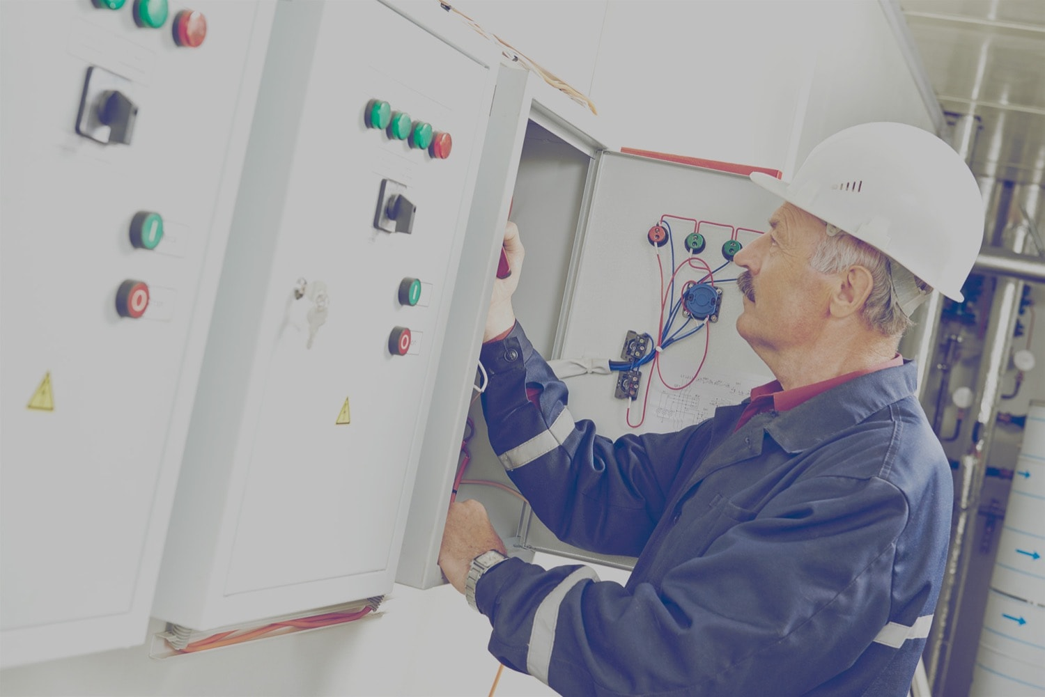 Construction worker making adjustments to an electrical panel.