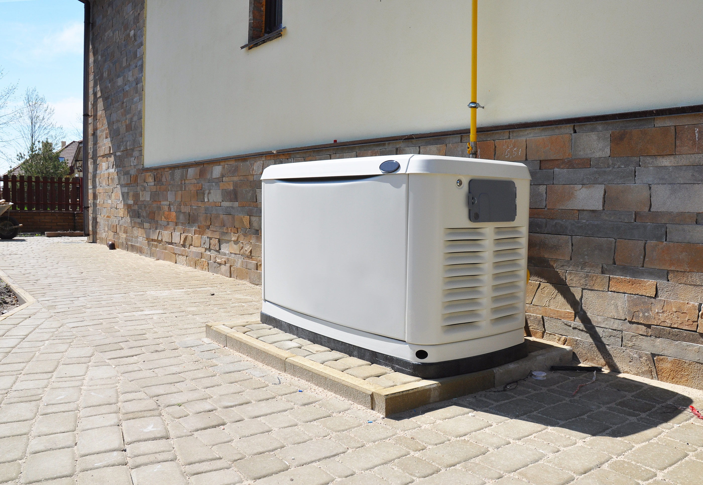 Propane-powered standby generator next to the exterior of a building.
