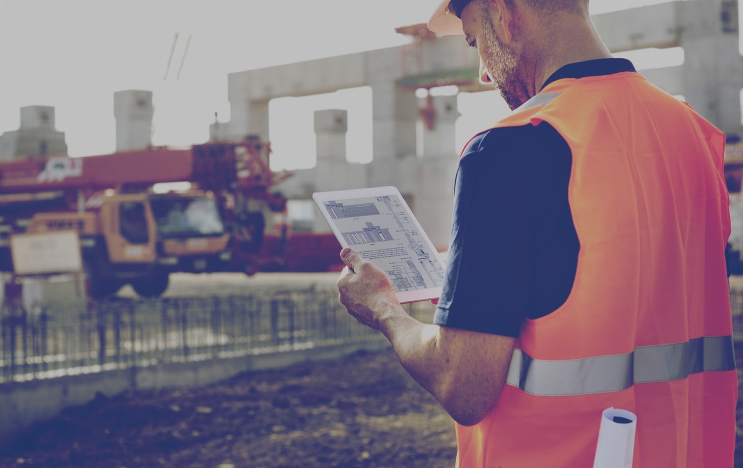 A construction worker on a job site looking at blueprints on a tablet.