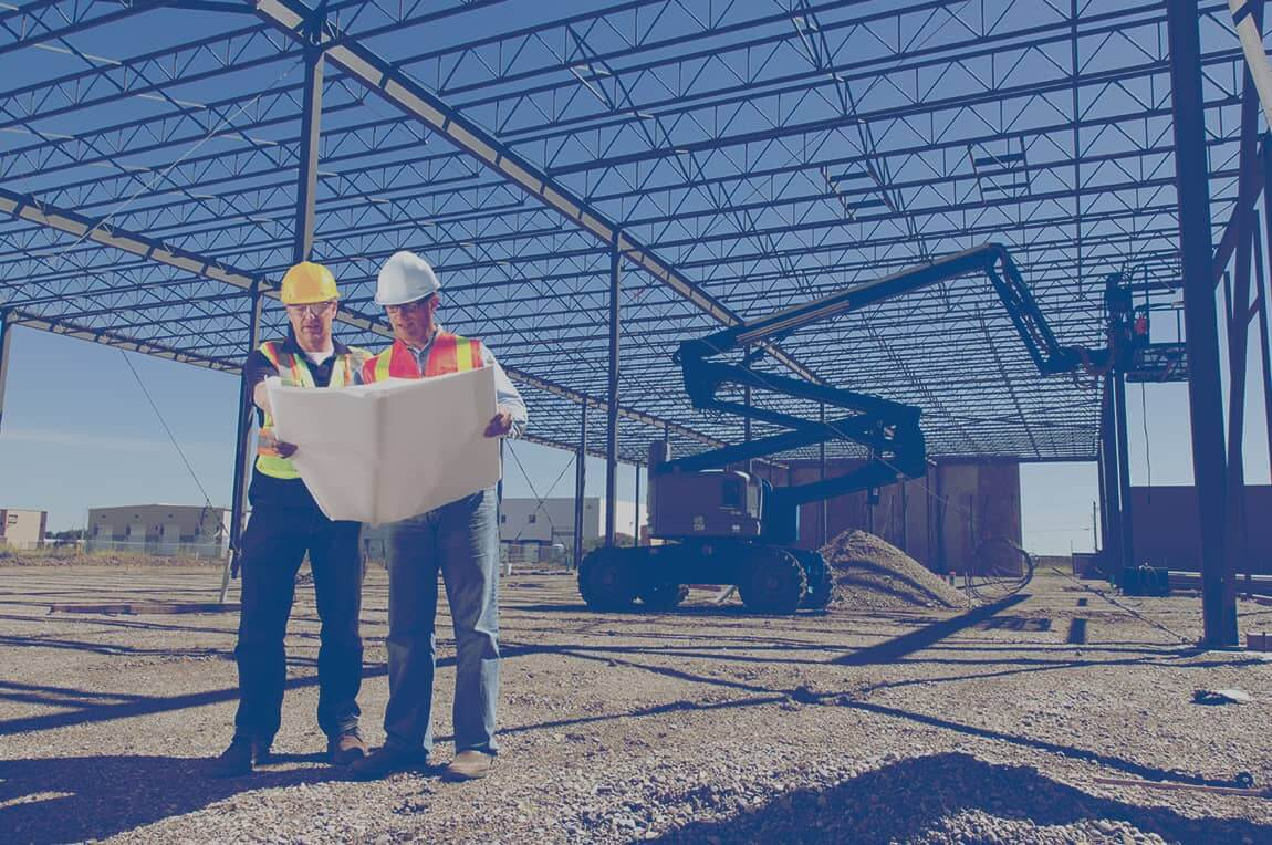 Two construction workers looking at a blueprint on the job site for a commercial building.