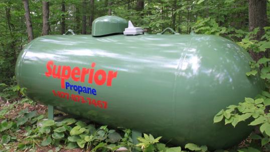 Green Superior Propane tank in a forest.