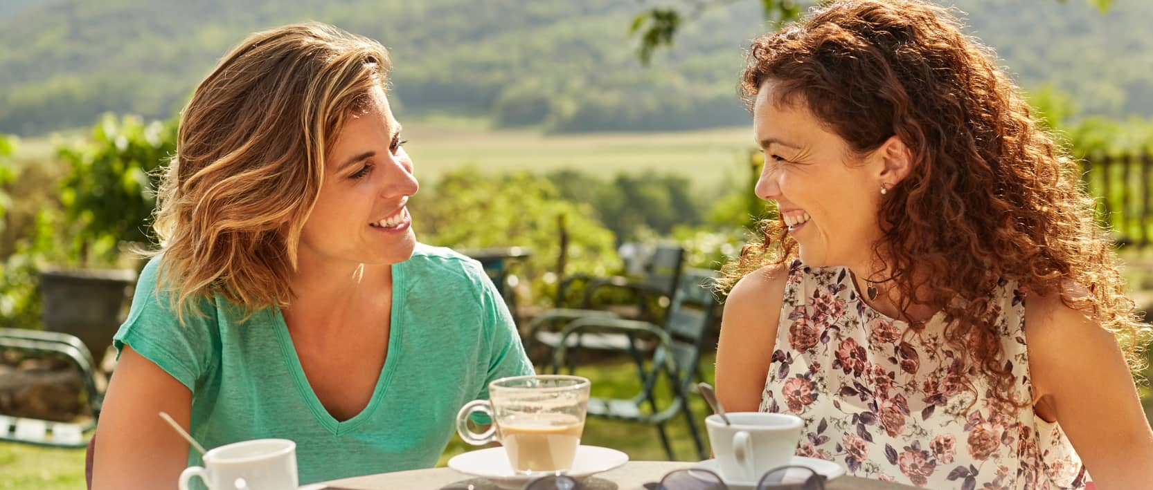 Two female friends at an outdoor patio drinking coffee on a sunny day. Click to learn about our refer a friend program.