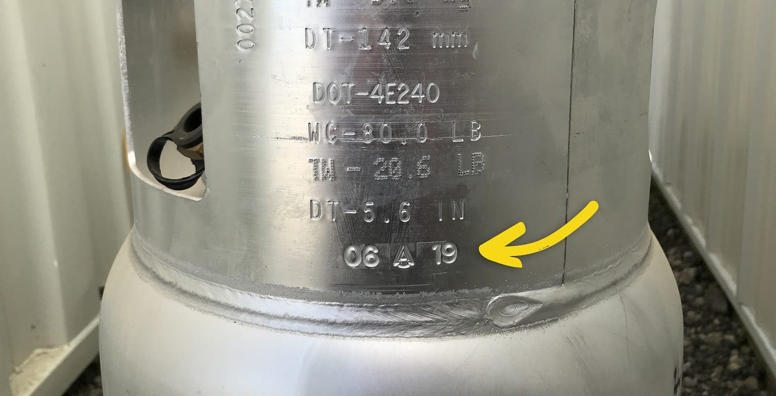 Closeup of a propane tank collar with an arrow pointing to the manufacturer's date stamp.