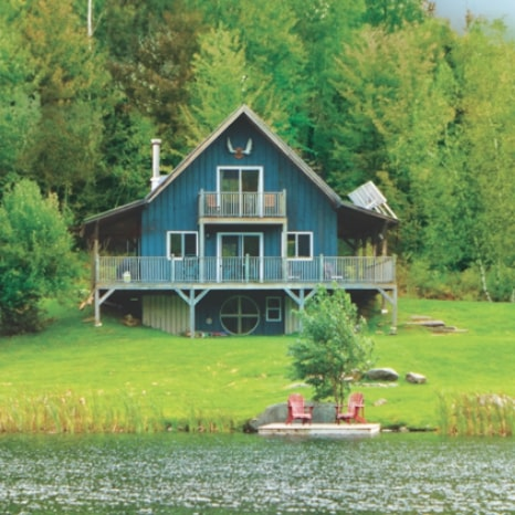 Blue cottage on a lake in a rural, forested location.