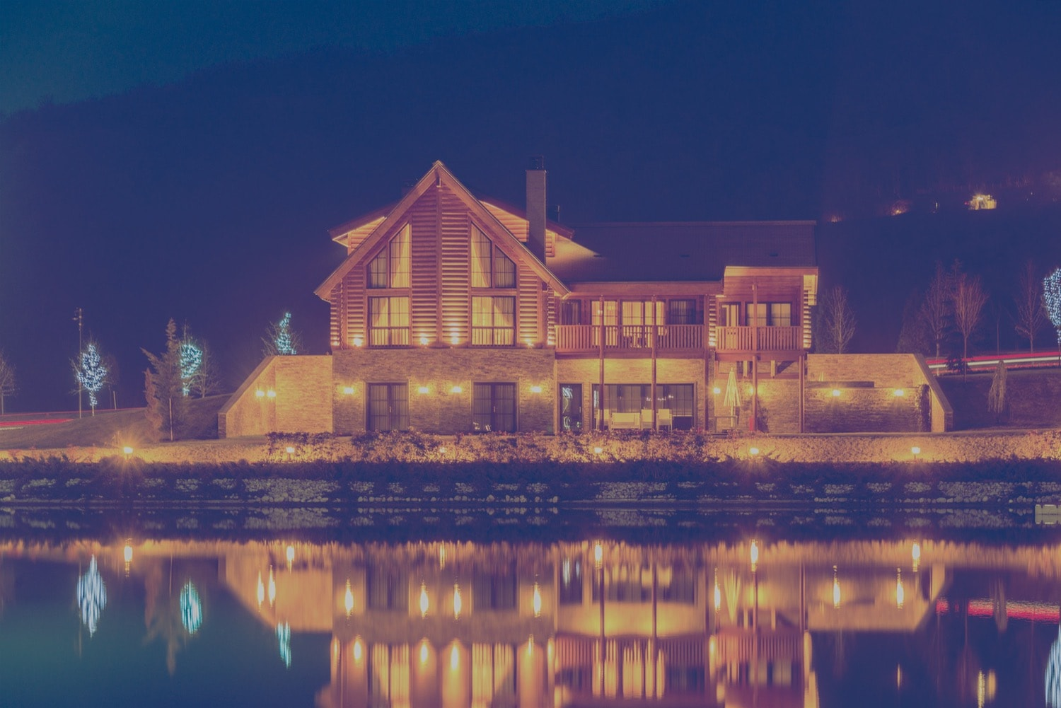 Large bed and breakfast home on a lake at night.