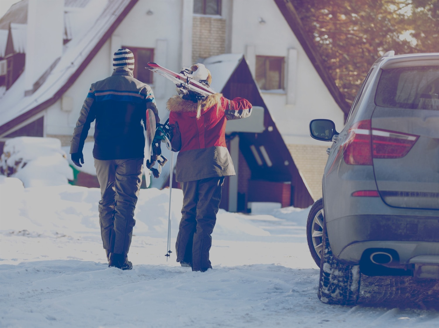 Couple walking into ski resort from the parking lot.