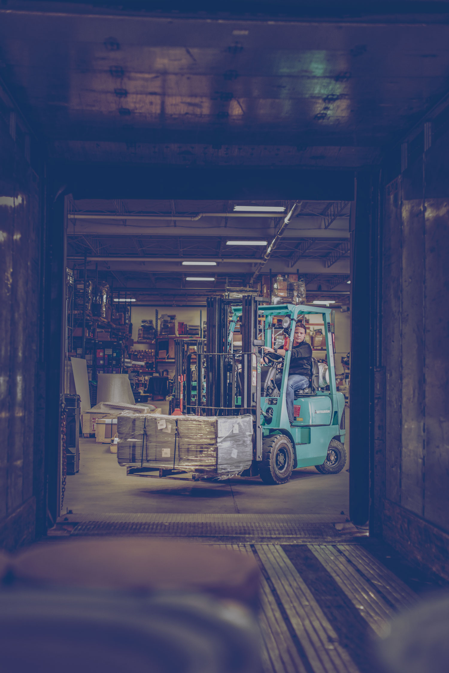 A propane-powered forklift in a warehouse filling a trailer with a pallet of goods.