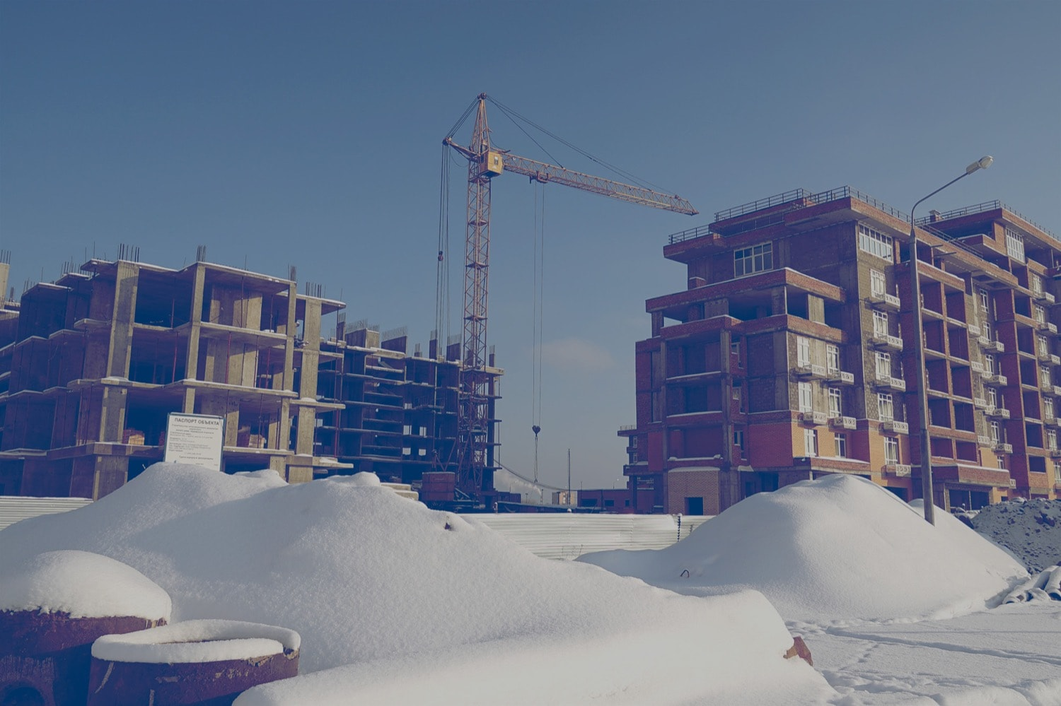 Two condos under construction with a crane in the background and snow on the ground.