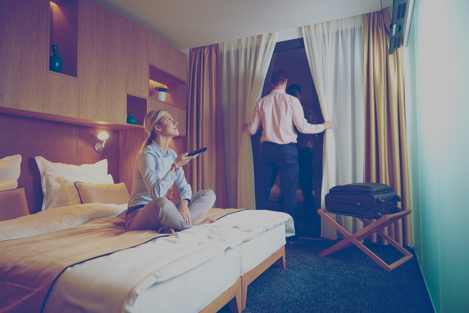 Couple in a hotel room. The woman is turning on a propane-powered heater, and the man is looking out the window.