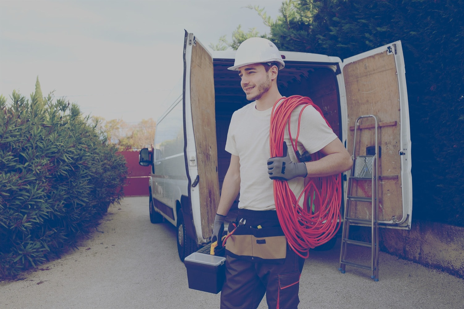 A male construction worker in a white hard hat carrying his tools from his van to the job site.