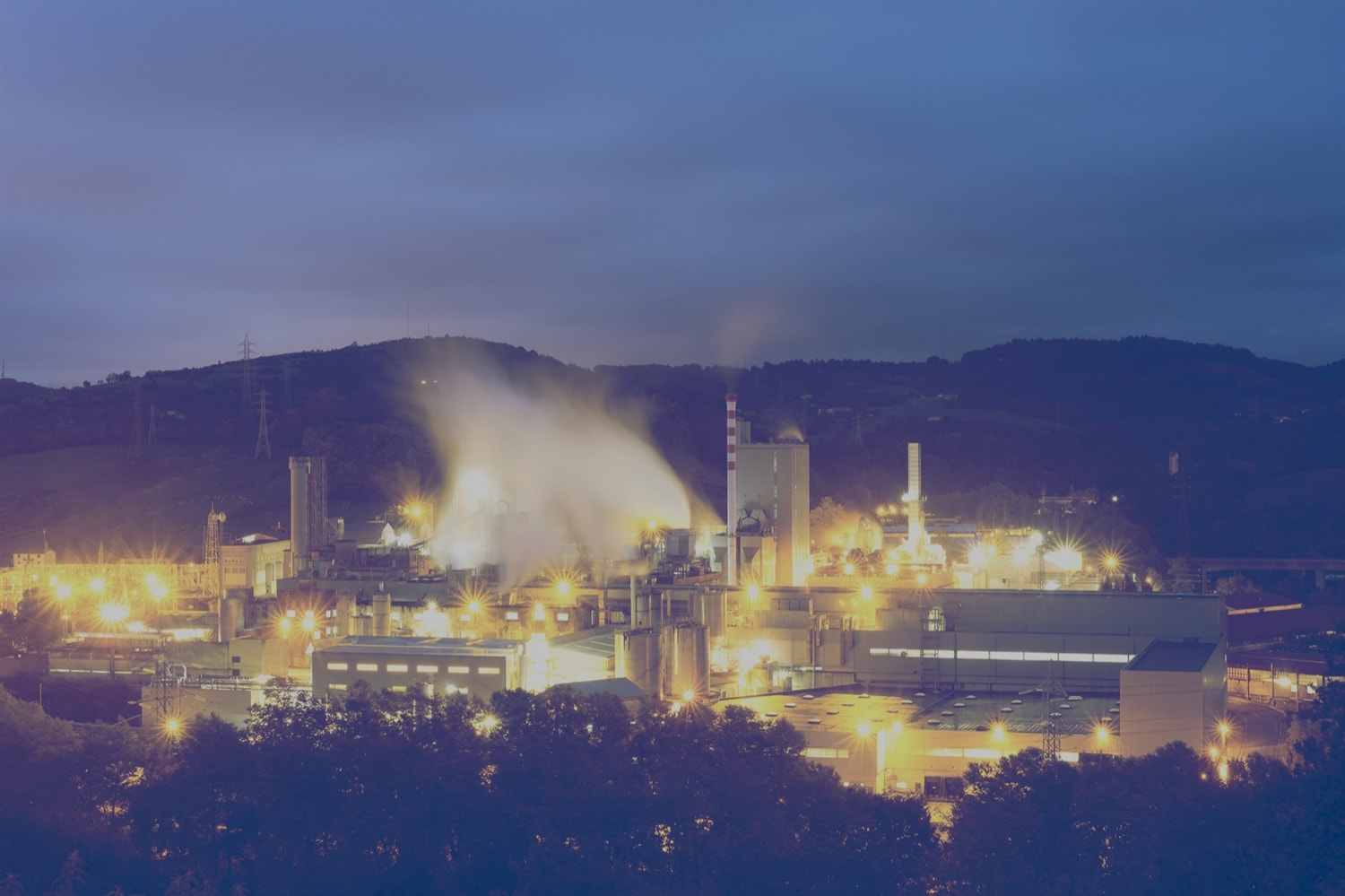 Panoramic view of an oil refinery lit up at night.