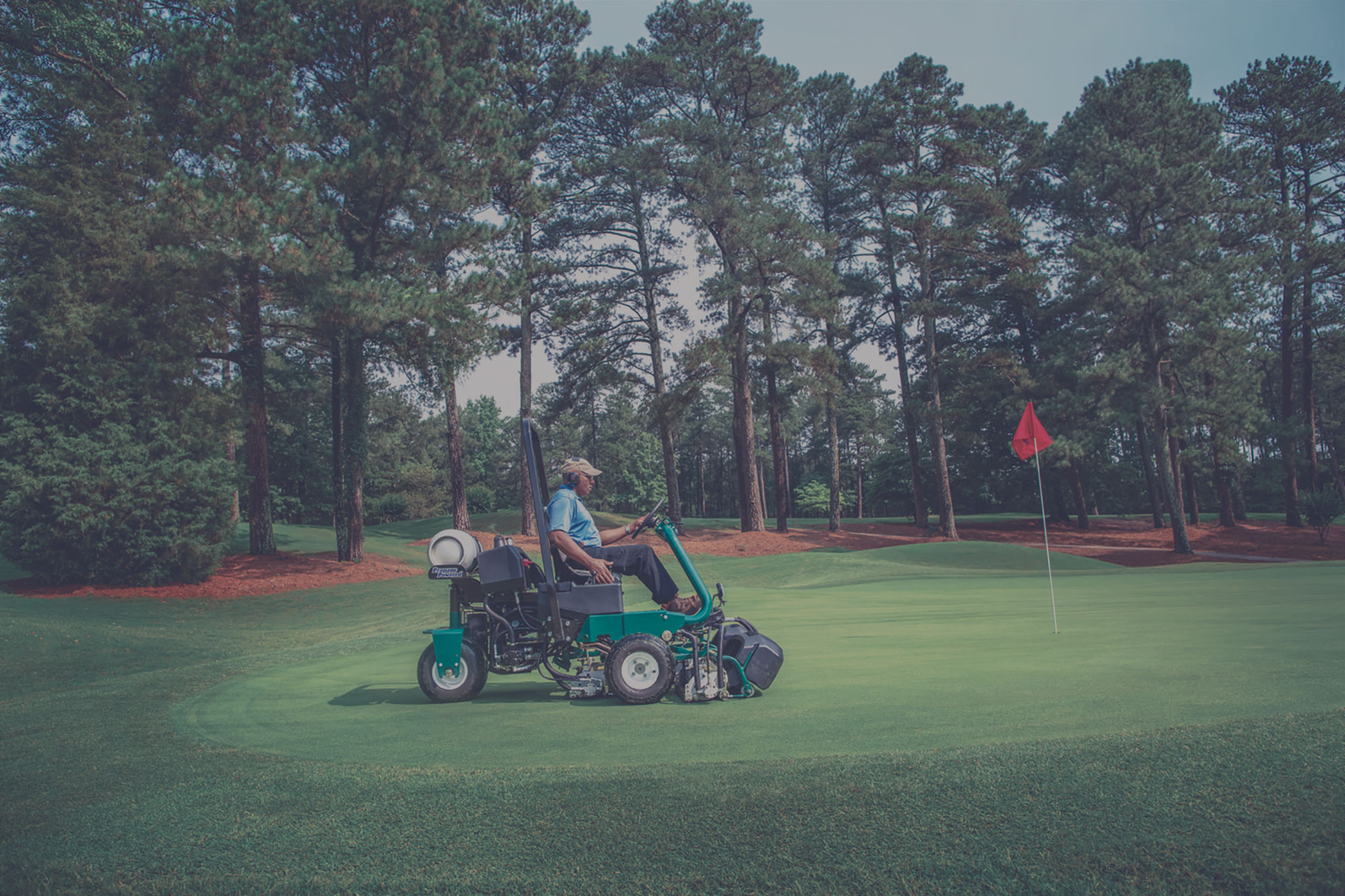 A man driving a propane-powered riding lawn mower at a golf course.