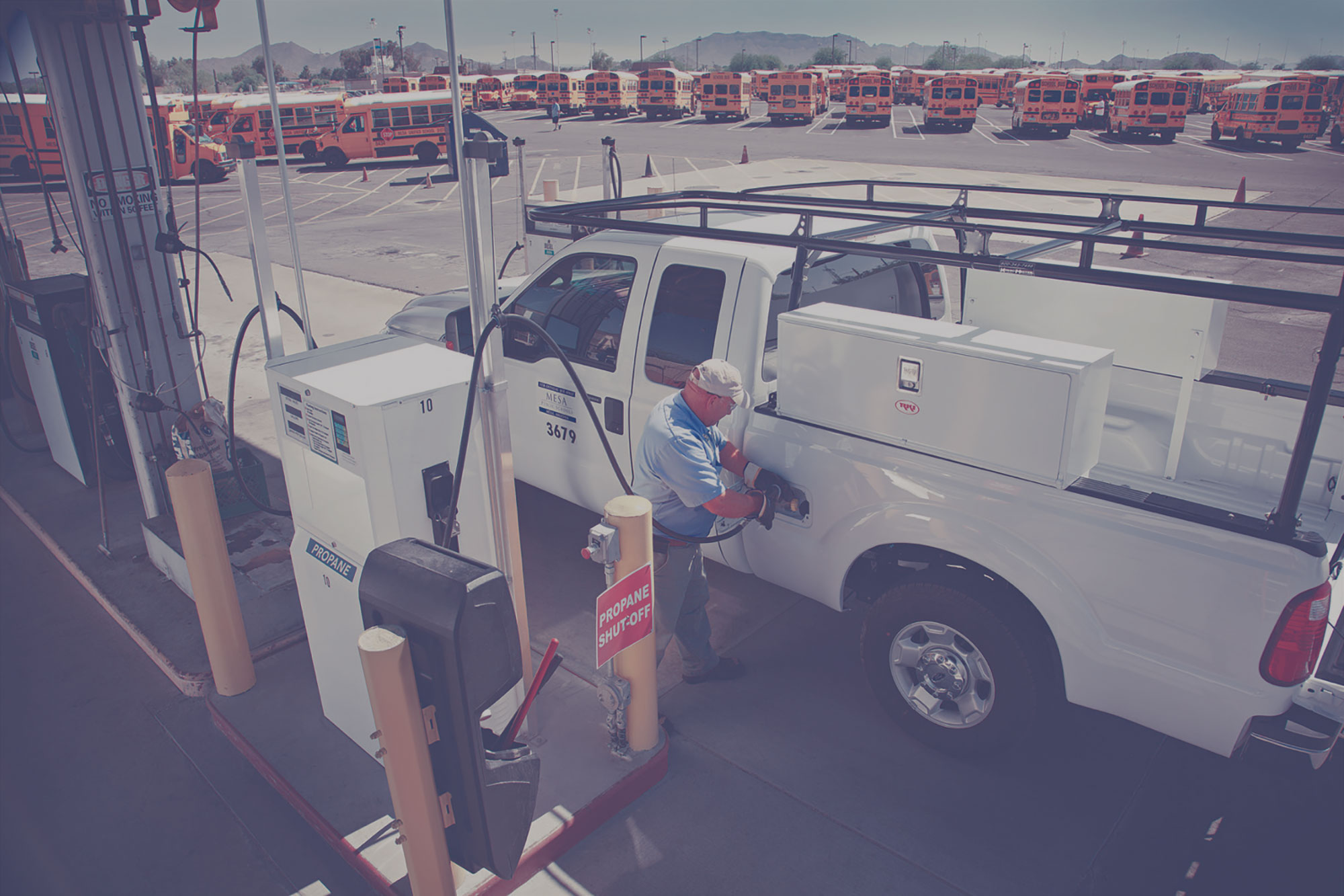 Man filling a pickup truck with propane autogas at a card lock station. There is a fleet of school buses in the background.