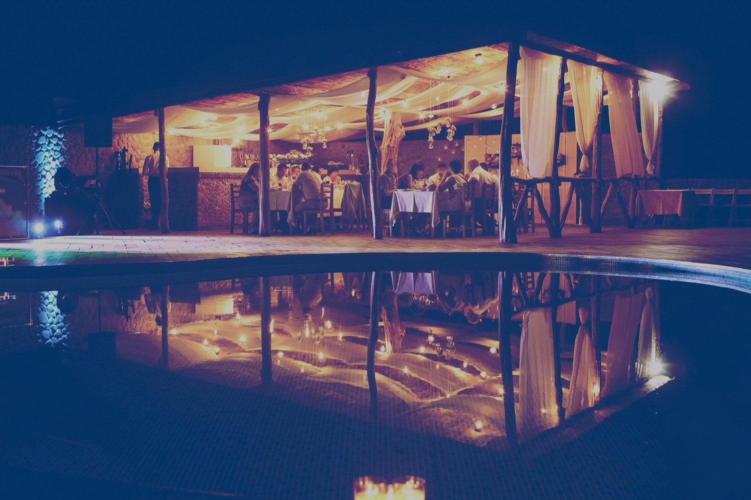 A large group of people eating a meal at night in an outdoor restaurant, next to a pool.