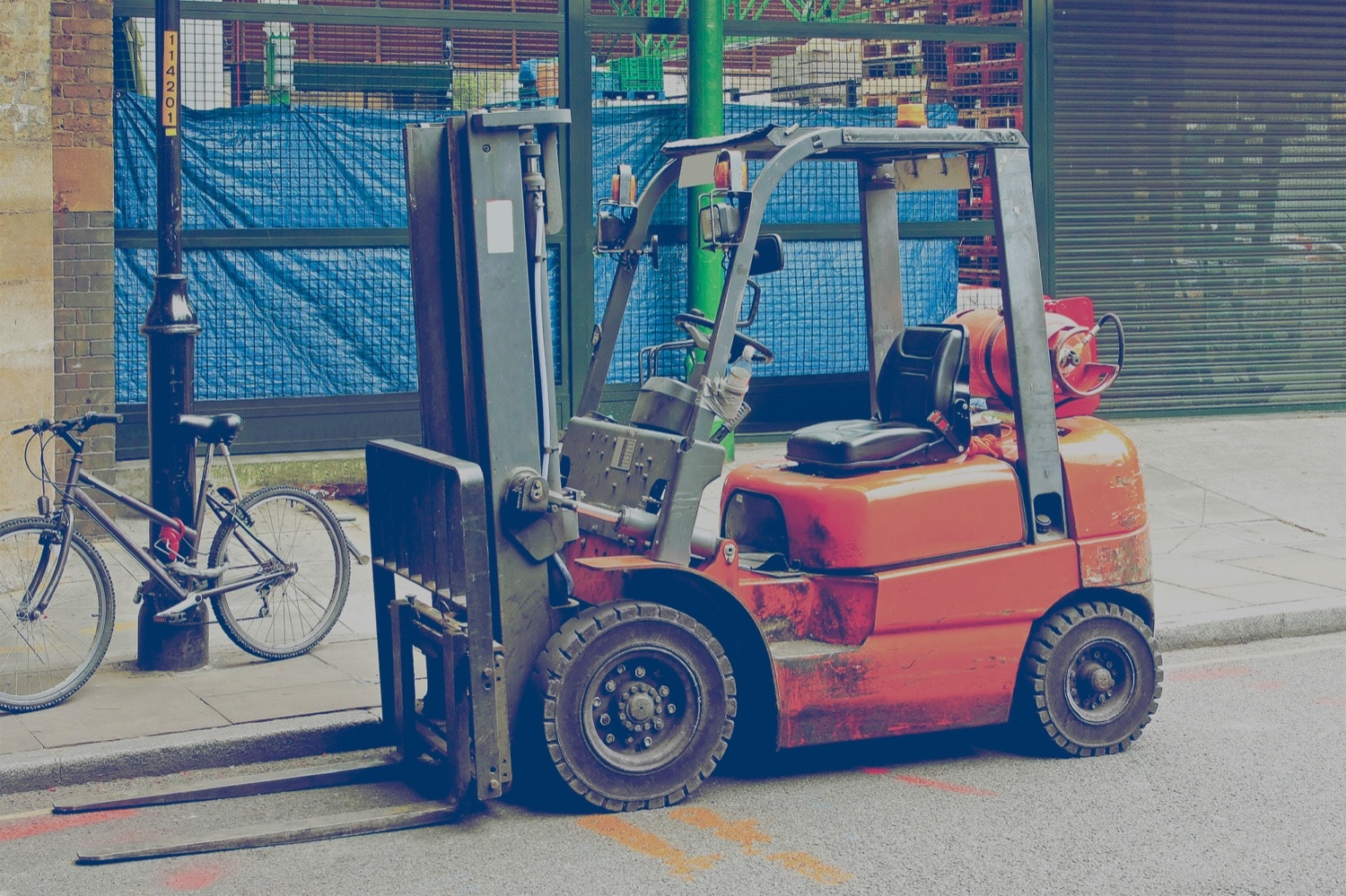 Orange forklift with propane cylinder parked on the street next to a bike.