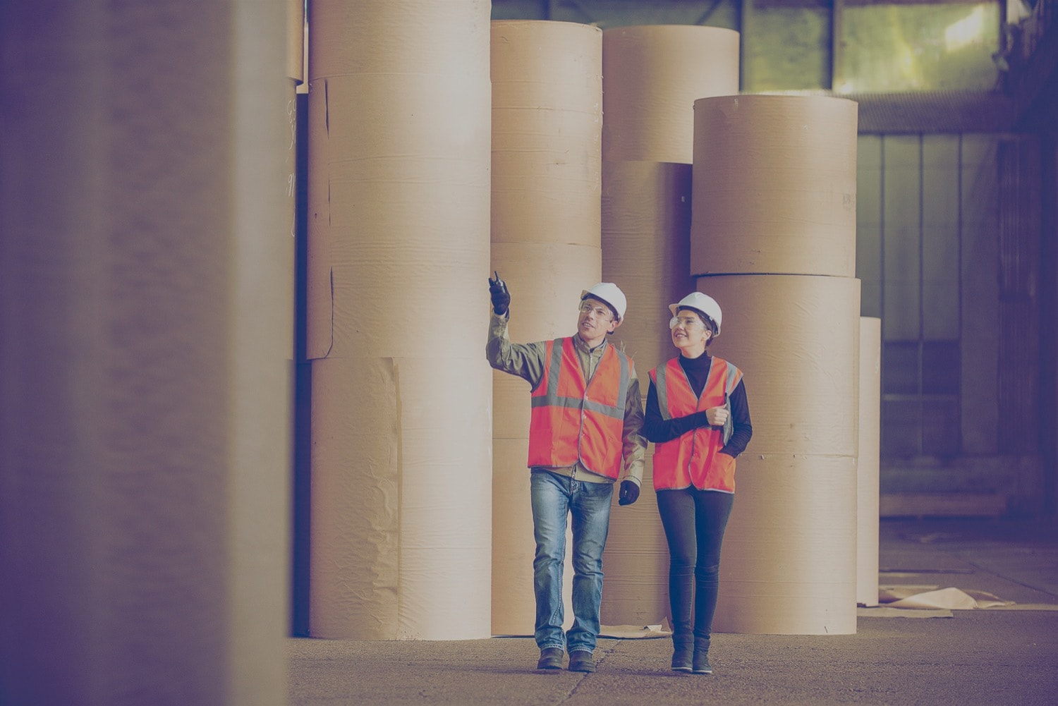 Two people in hardhats walking through an industrial room with rolls of carpets.