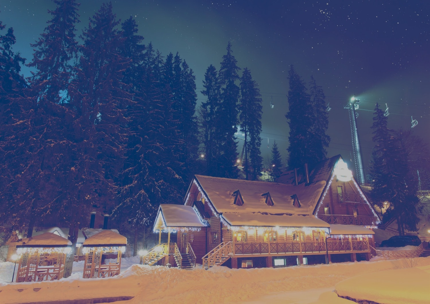 Ski Chalet and lift in the middle of the night, covered in snow.