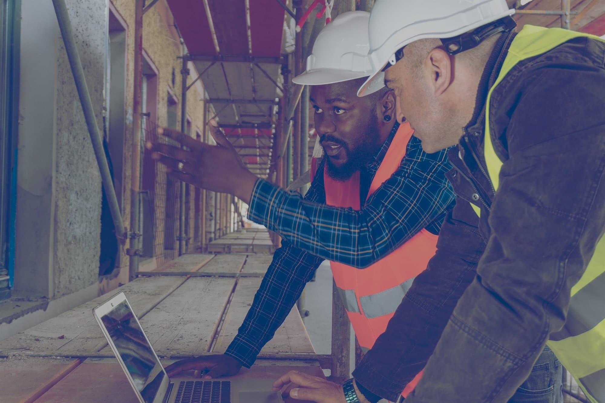 Two Superior Propane partners looking at a laptop at a construction site.