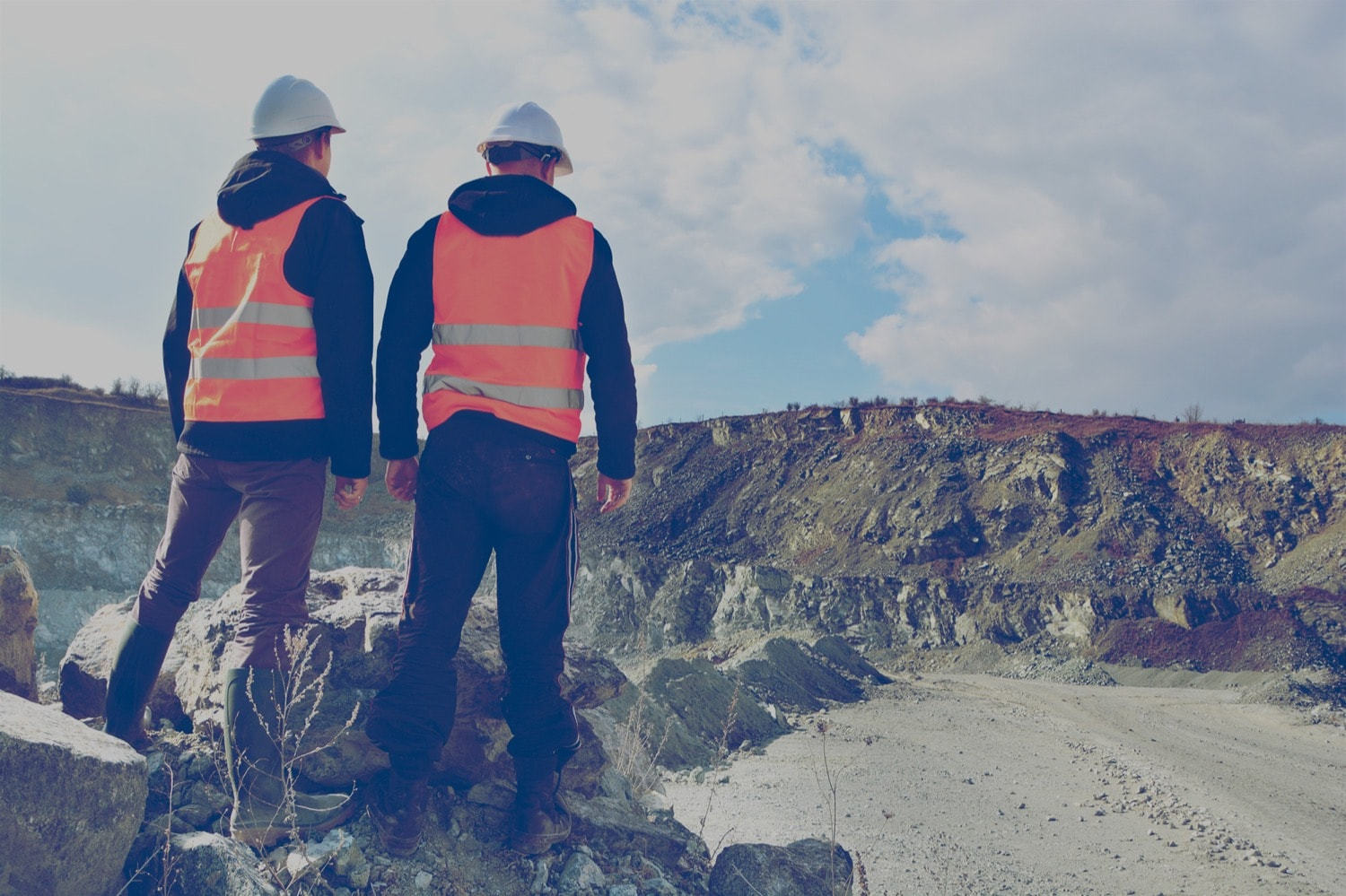 Two construction workers look at an expansive open-pit mine.