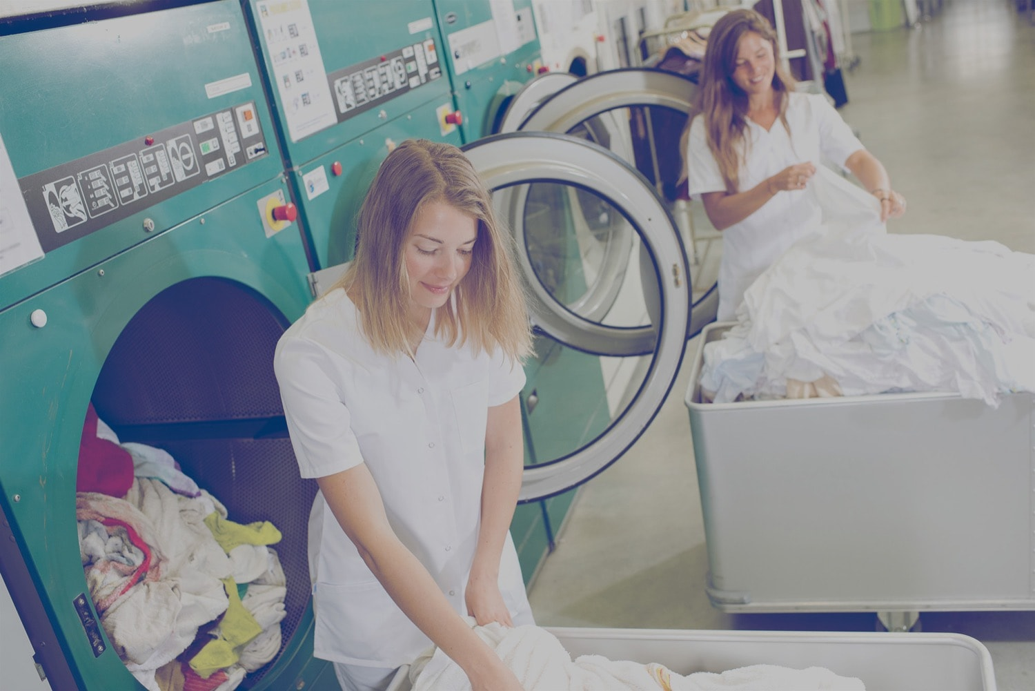 Two workers in a laundry room in a hotel. They are grabbing linens to put in the dryer.