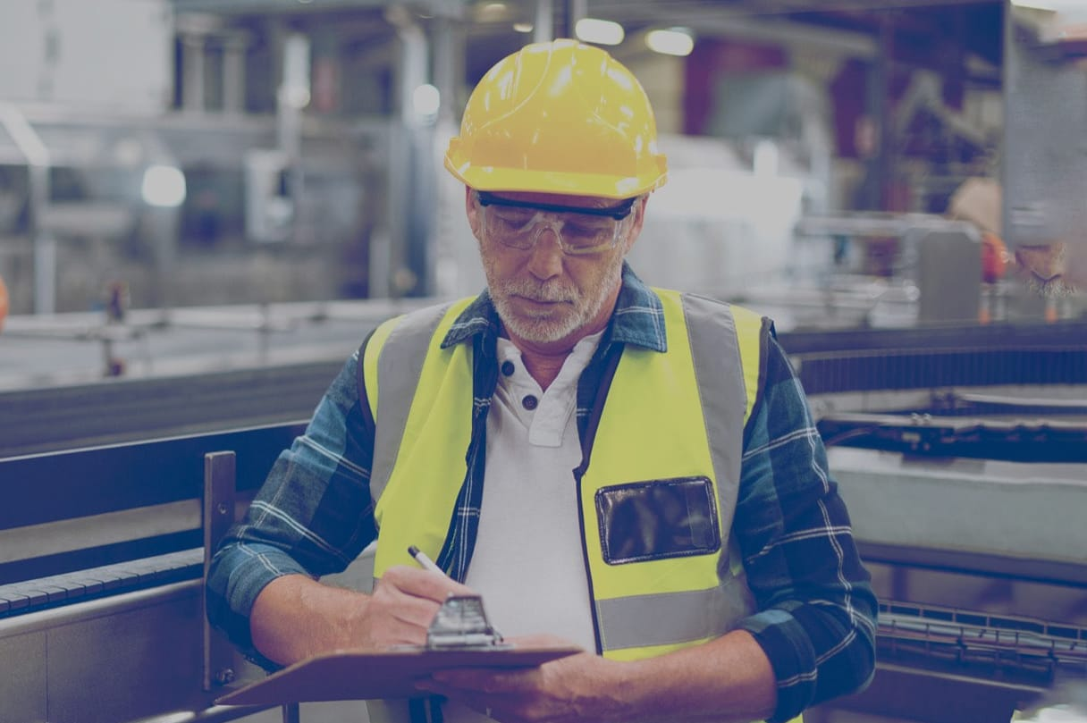 A safety inspector in an industrial plant looking at a clipboard.