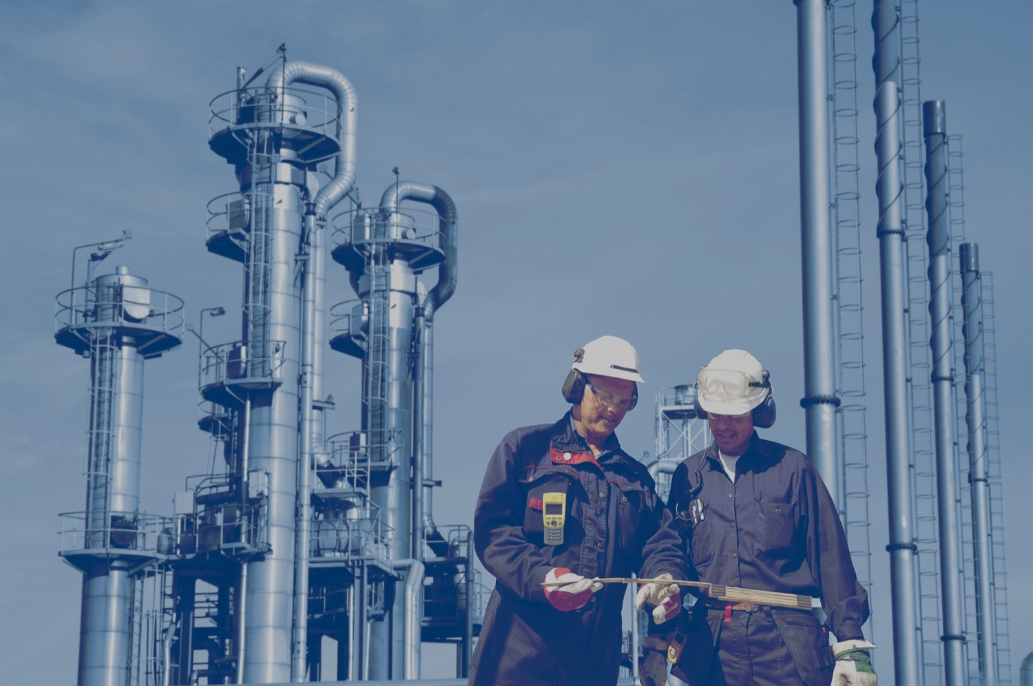 Two workers in an oil field with a refinery in the background.