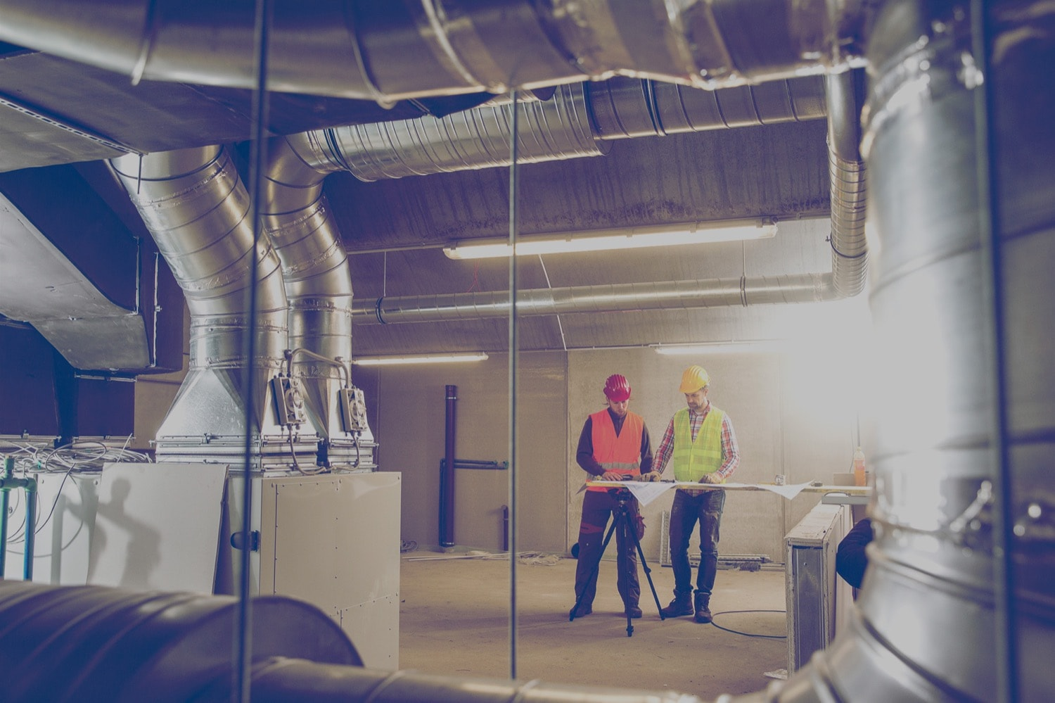 Workers looking at blueprints in an industrial propane furnace room.