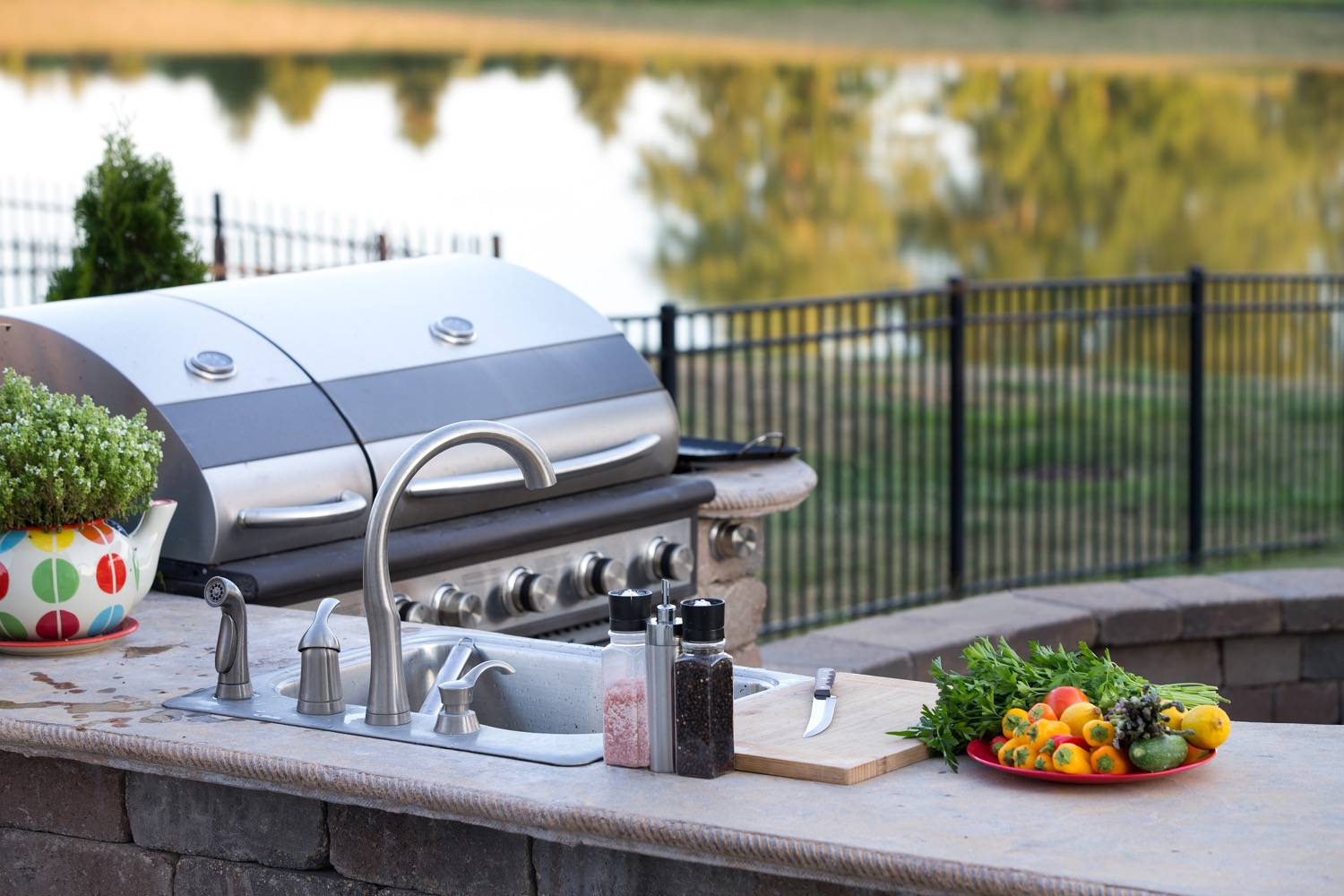 An outdoor residential kitchen with a sink and propane grill situated next to a lake.