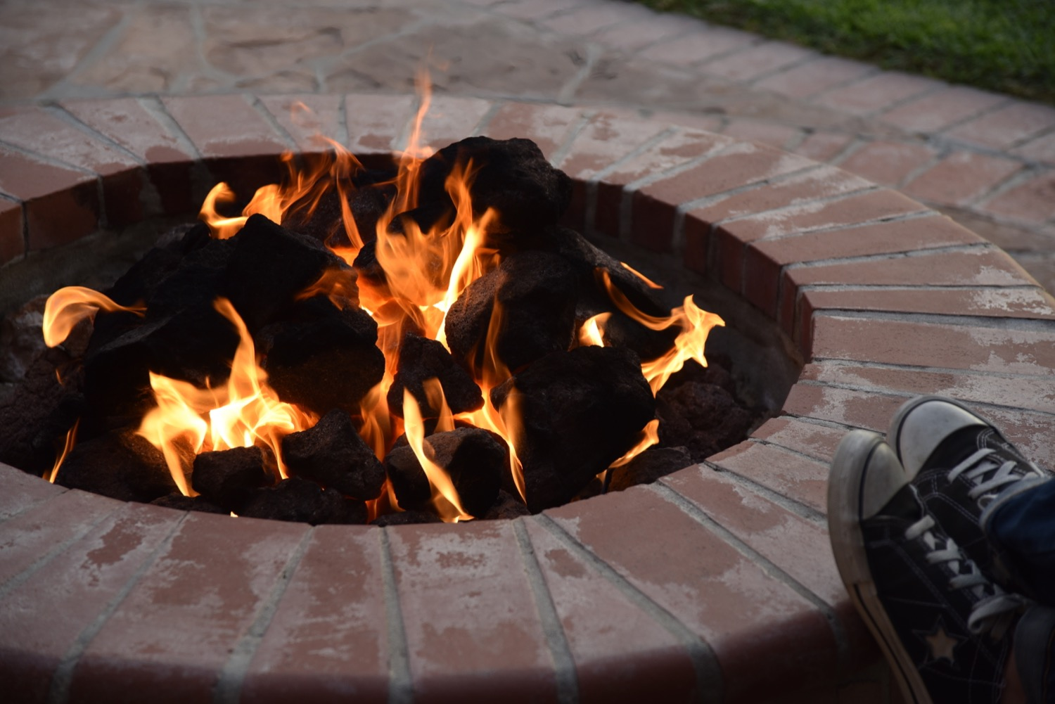Person sitting next to a propane-powered outdoor fire pit made of brick.