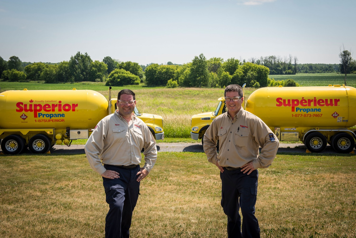 Two Superior Propane employees standing in front on their trucks on a sunny day.