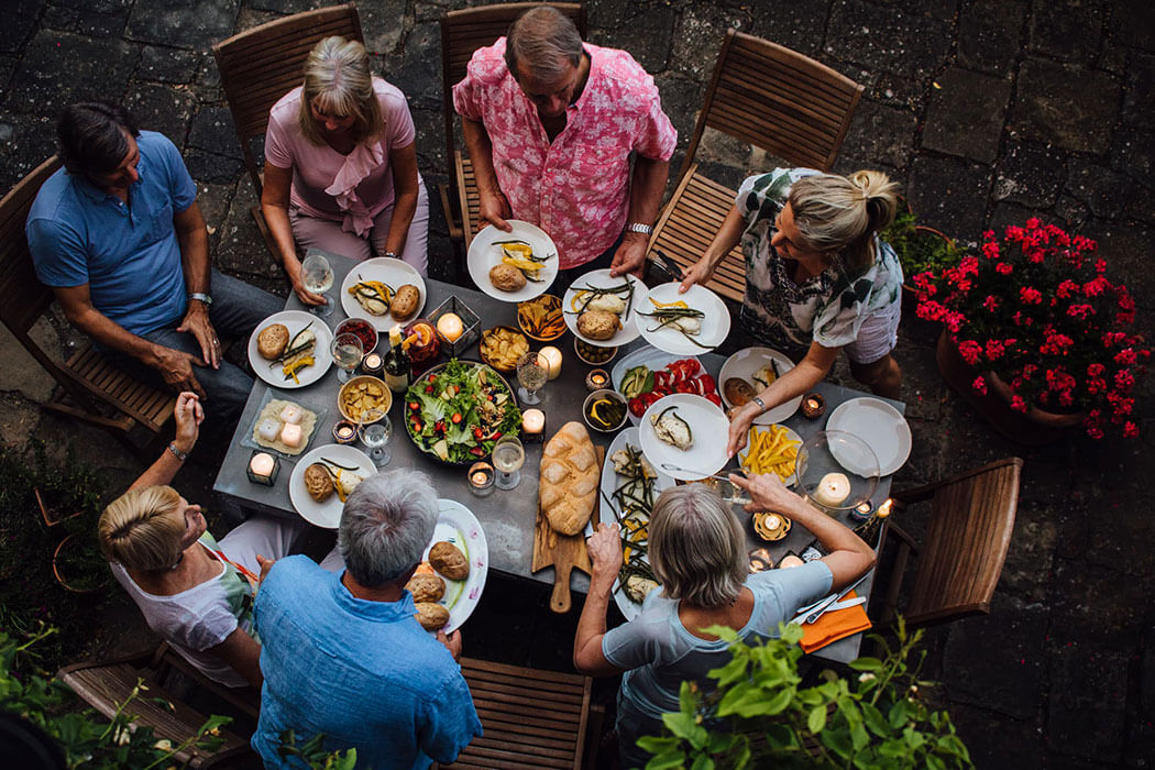 An overhead look at a group of adults sharing a large meal on an exterior patio that is heated by propane.