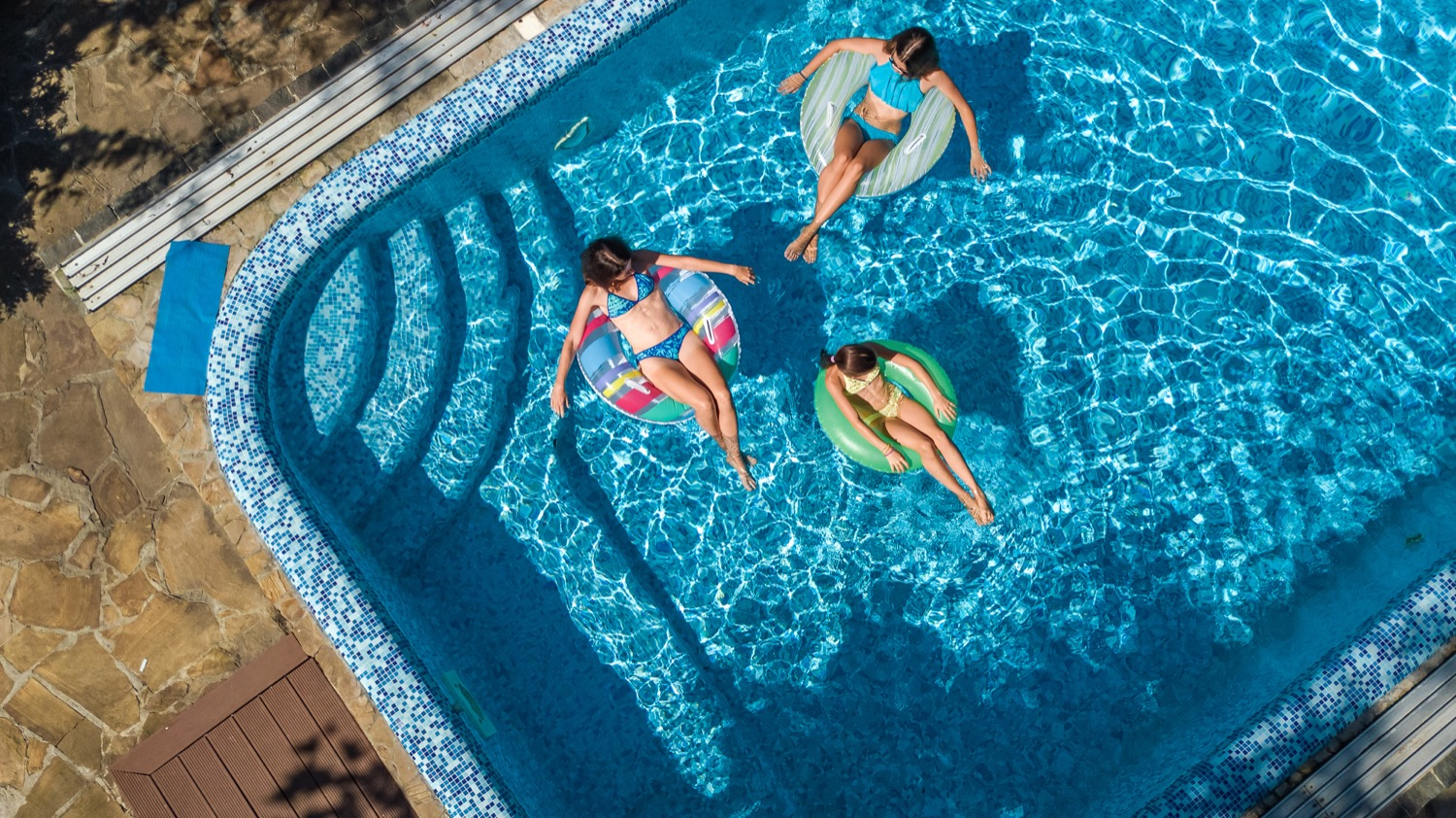 Three girls relaxing on inflatable floaties in a pool.