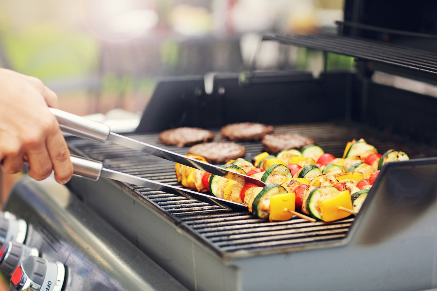 Barbequing vegetable kabobs and burgers on a propane grill.