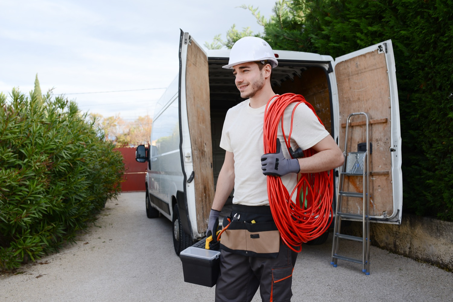 A contractor with a white hard hat holding a toolbox and extension cord, standing behind his work van.