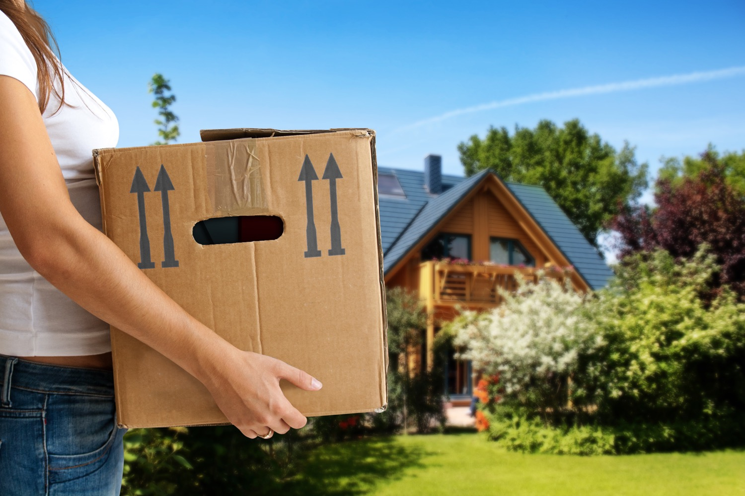 Woman holding a cardboard box in front on a home.