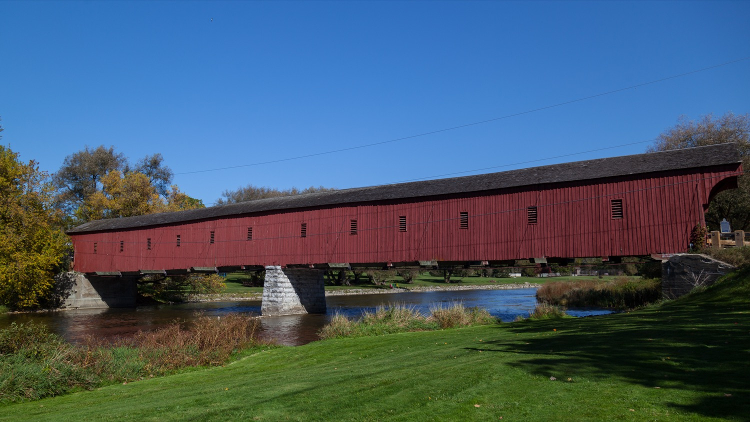 Red covered bridge over a river in a rural area.