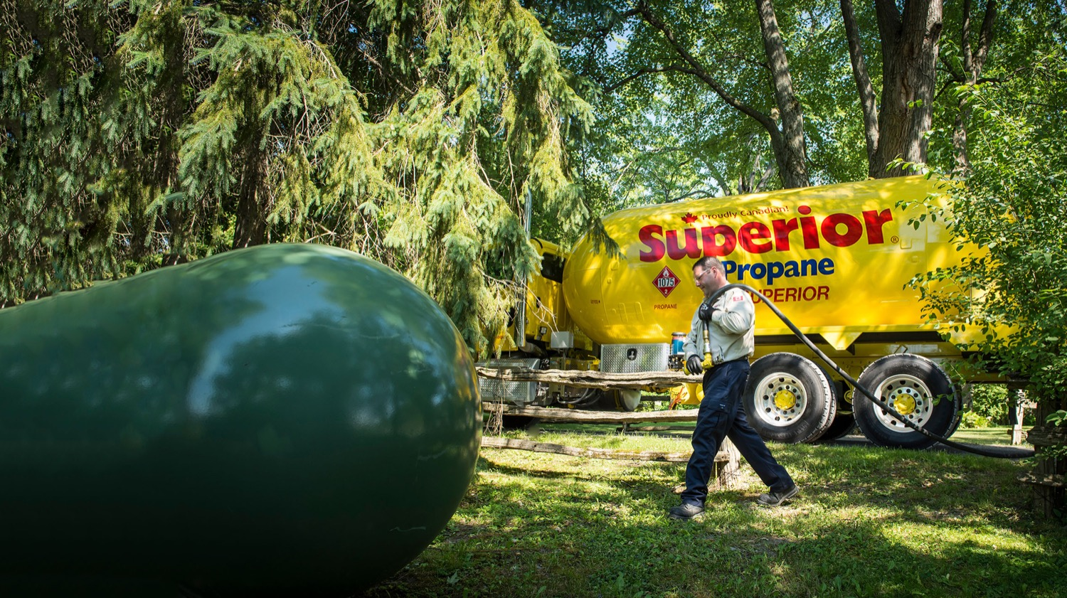 Superior Propane employee preparing to refill a green propane tank in a forested area.