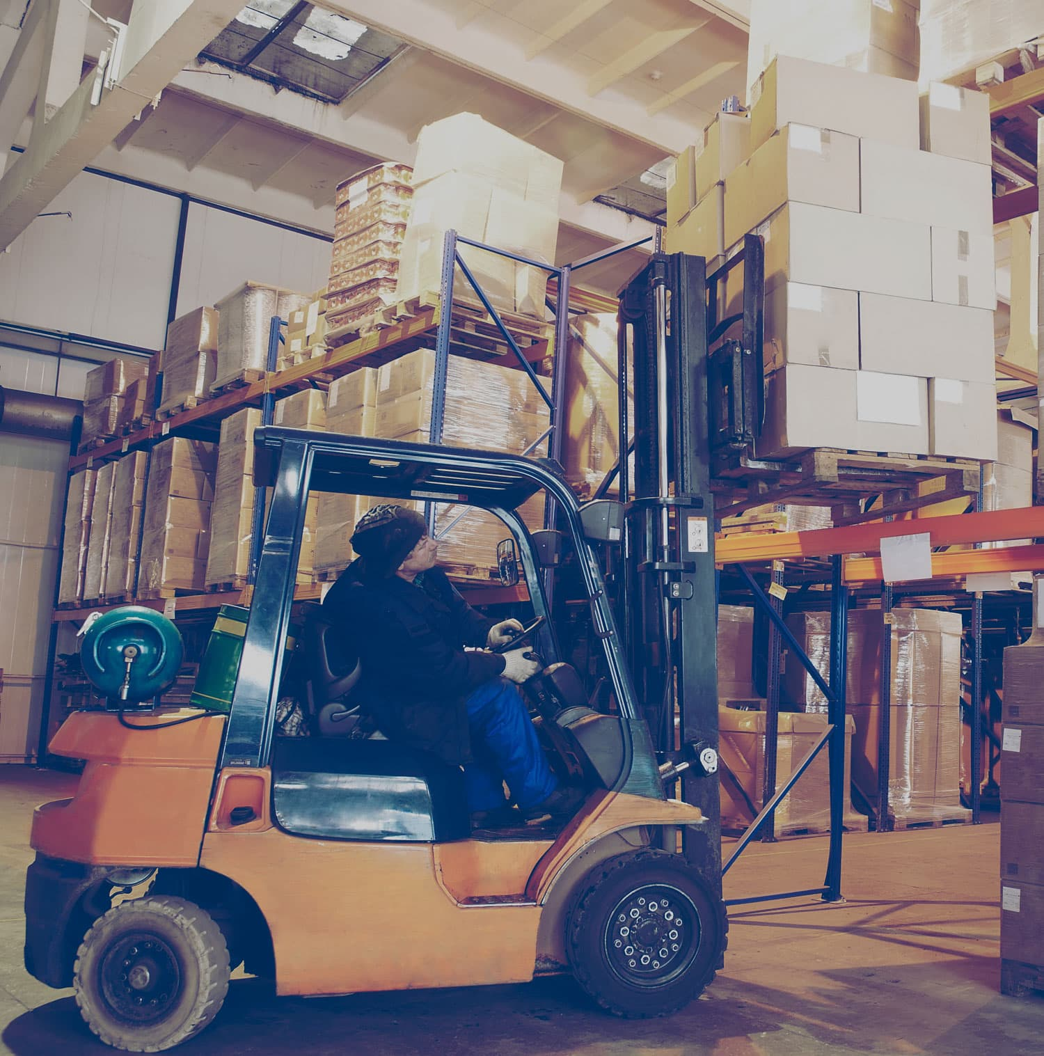 Man placing a skid of boxes on a storage shelf using a forklift.