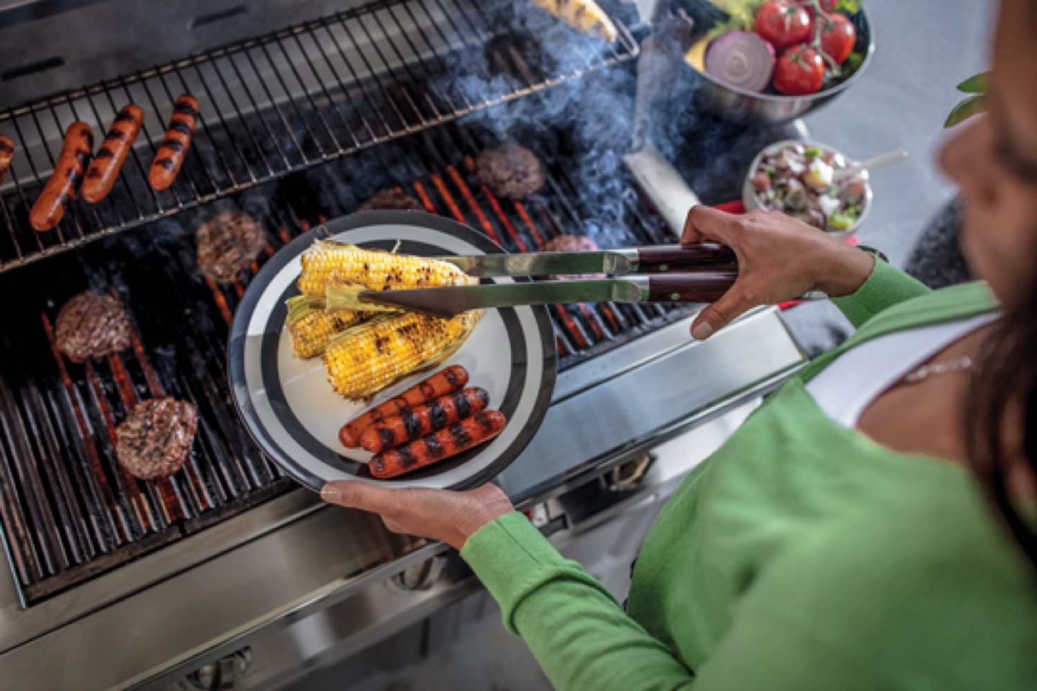 Woman removing corn and hotdogs from a propane barbeque and placing them on a plate.