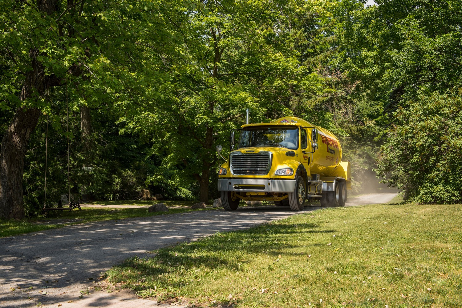 Superior Propane truck making a delivery to a home on a tree-lined rural dirt road.