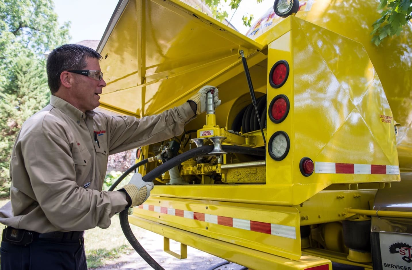 A Superior Propane employee preparing the hose from the truck to start refilling a tank.