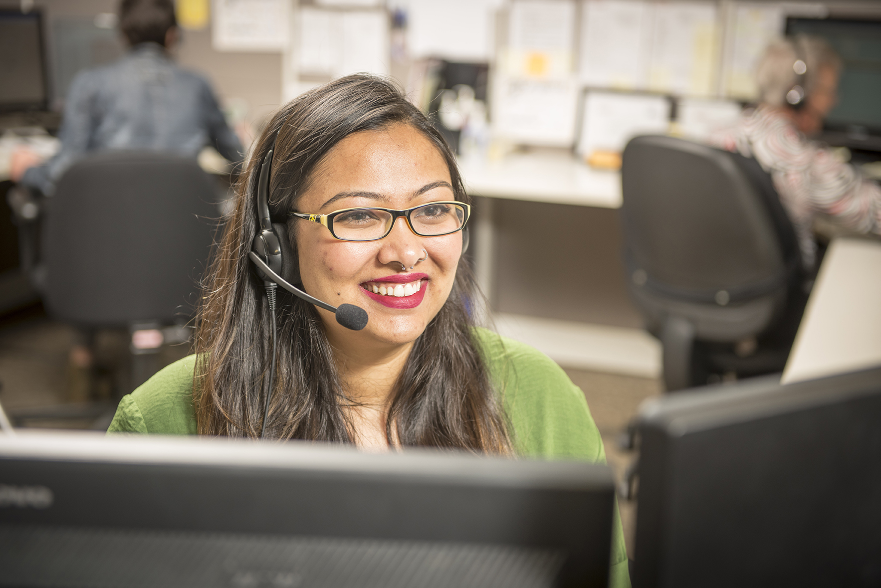 Smiling customer support representative with hands-free headset working in the office